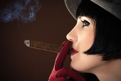 Fashionable woman smokes a cigar Royalty Free Stock Images