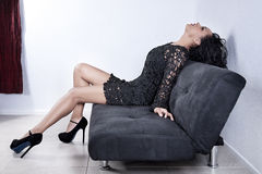Fashionable woman on sofa. Side view of fashionable young woman in short dress relaxing on modern sofa or couch Stock Photos