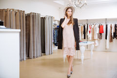 Fashionable woman standing in clothig shop Stock Photo