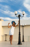 Fashionable woman standing beside street lamp stock photography