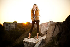 Fashionable woman standing on top of hill Stock Photos