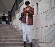 MILANO, Italy: September 21, 2018: Fashionable woman in street style outfit on Arengario stairs royalty free stock images