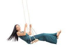 Fashionable woman swinging on a wooden swing Royalty Free Stock Photography