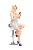 Fashionable woman texting on a cell phone. Isolated on white background Stock Photo