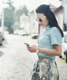 Fashionable woman texting on the street Royalty Free Stock Photography