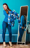 Fashionable woman trying plaid shirt in front of mirror Stock Photography