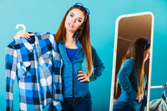 Fashionable woman trying plaid shirt in front of mirror Royalty Free Stock Photography