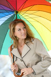 Fashionable woman under a rainbow coloured umbrella Stock Photo