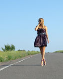 Fashionable woman walking on a country road Stock Photo