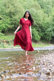 Fashionable woman walking in a river alone Royalty Free Stock Image