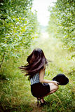 Fashionable woman waving her hair in green forest Royalty Free Stock Photos
