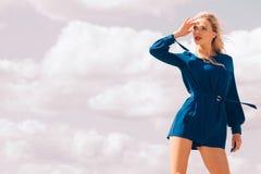 Fashion model wearing blue jumpsuit. Fashionable woman wearing blue jumpsuit shorts perfect for summer. Fashion model outdoor photo shoot Royalty Free Stock Photo