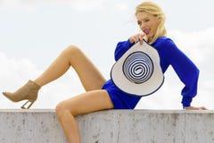 Fashion model wearing blue jumpsuit. Fashionable woman wearing blue jumpsuit shorts perfect for summer holding elegant stylish sun hat. Fashion model outdoor Stock Images