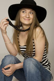 Fashionable woman wearing hat. Portrait of happy, fashionable young woman wearing wide brimmed hat, studio background Royalty Free Stock Photography