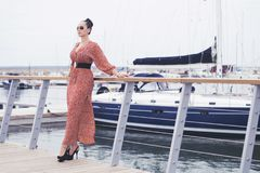 Fashionable woman wearing long red dress in sunglasses taking a walk near sea, pier with yachts. Fashionable brunette woman wearing long red dress in sunglasses Royalty Free Stock Image