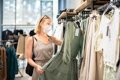 Free Fashionable Woman Wearing Protective Face Mask Shopping Clothes In Reopen Retail Shopping Store. New Normal Lifestyle Stock Images - 196398434