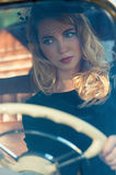 Fashionable woman at the wheel of a retro car Royalty Free Stock Image