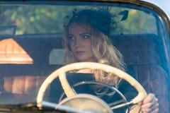 Fashionable woman at the wheel of a retro car Stock Photos