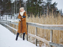 Fashionable woman and winter clothes - rural scene. Fashionable mature adult woman wearing winter clothes and she standing next to the fence - rural scene Stock Photo
