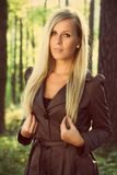 Fashionable womans portrait. Blonde in a coat in the woods and holds the hair ends Royalty Free Stock Images