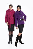 Fashionable Women. Young women in a raincoat on isolated background royalty free stock photos