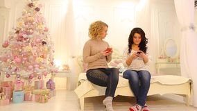 Fashionable women look at mobile screens and do personal things, sitting on bed in bright bedroom with Christmas tree on stock video