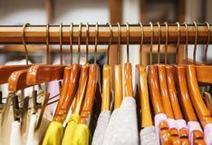 Fashionable women`s clothing on wooden hangers in a modern clothing store. Stylish clothes for girls and women. Shopping and sale. The clothing store Stock Images