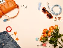 Fashionable Women`s Cosmetics and Accessories. Falt Lay. Nail Polish and blush. Jewelry and Rings. A bouquet of flowers. Orange roses. Handbag and Denim Jacket Royalty Free Stock Photography