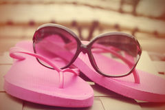 Fashionable women's sunglasses and pink flip flops Stock Photo