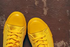 Yellow gym shoes closeup on an old shabby background. Fashionable yellow sports shoes or gym shoes closeup and separately on an old dirty shabby brown background stock image
