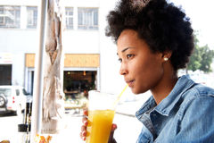 Fashionable young african woman sipping orange juice Royalty Free Stock Images
