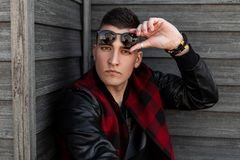 Fashionable young american hipster man in a plaid jacket in stylish sunglasses in a t-shirt poses near a wooden brown building. On a spring day. Handsome stock photos