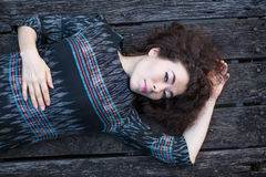 Fashionable young asian woman lying on a wooden platform. Relax. Stock Image