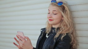 Fashionable young and beautiful girl with a smartphone in hands. The girl is looking at the phone screen. Against a stock video