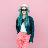 Fashionable young blogger woman with blue hair wearing casual style outfit with black jacket, white hat, pink jeans and sunglasses. Posing near the wall Stock Photo