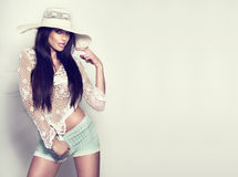 Fashionable young brunette girl posing in white hat. Photo of fashionable brunette woman wearing white hat in sunny day Royalty Free Stock Image