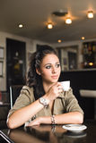 Fashionable young brunette woman having coffee. Royalty Free Stock Image