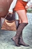 Fashionable young Caucasian woman with long legs wearing orange shorts, suede brown knee boots and holding a bag walking on city Royalty Free Stock Image