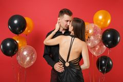 Fashionable young couple in black clothes celebrating birthday holiday party on bright red background air