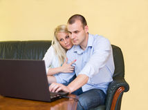 Fashionable young couple having fun with laptop. Stock Photos