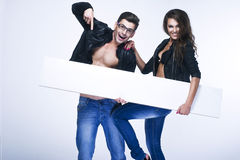 Fashionable young couple holding white board Stock Image