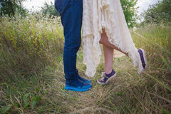 Fashionable young couple in sneakers on nature, legs, lifestyle-concept Royalty Free Stock Image