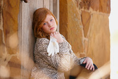Fashionable young girl. Fashionable young red haired girl leaning against wooden door of home Stock Images
