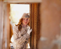 Fashionable young girl. With fur hat looking through door Royalty Free Stock Image