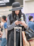Fashionable young girl busy with her smart phone, Beijing, China. BEIJING-MAY 21, 2016. Fashionable girl with smartphone. China mobile internet market will royalty free stock photos