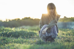 Fashionable young girl crouching in sheer dress and jacket. Staring at camera in a meadow Royalty Free Stock Photos