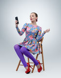 Fashionable young girl in dress sitting on chair making selfie Stock Photography