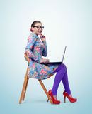 Fashionable young girl in glasses sitting on a chair with laptop. Oops! Royalty Free Stock Image