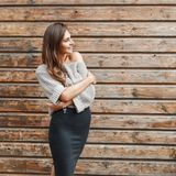 Fashionable young girl in a gray sweater and black skirt near. The wooden wall stock photo