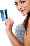 Fashionable young girl holding up a credit card Royalty Free Stock Photography